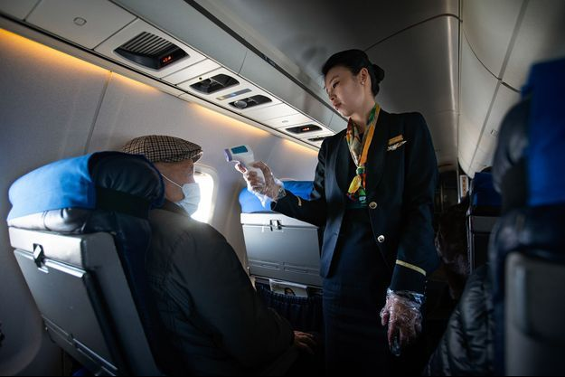 Une hôtesse de l'air contrôle la température d'un passager.