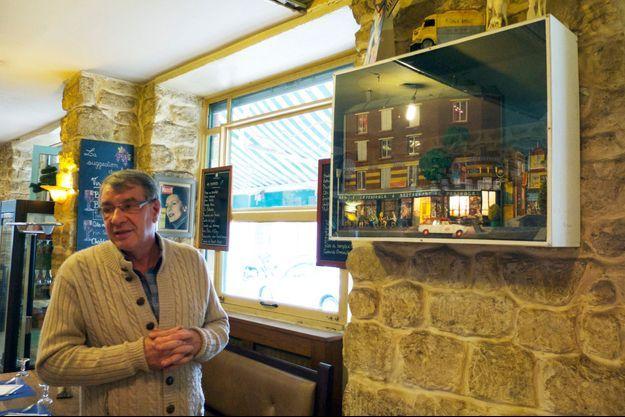 """Dani dans son restaurant """"La Péricole"""" à Saint-Ouen. Au mur, une maquette de la façade de son établissement avec une voiture siglée du logo """"Paris Match""""."""