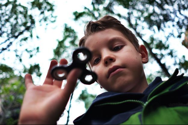 Un enfant s'amuse avec un hand spinner.