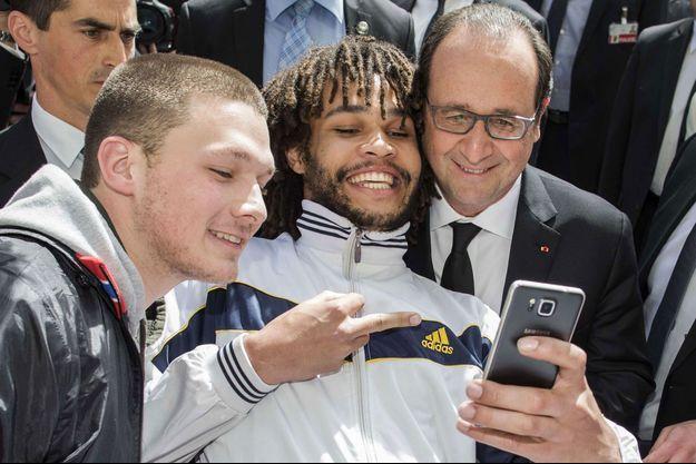 Un homme fait un doigt d'honneur à François Hollande pendant un selfie.