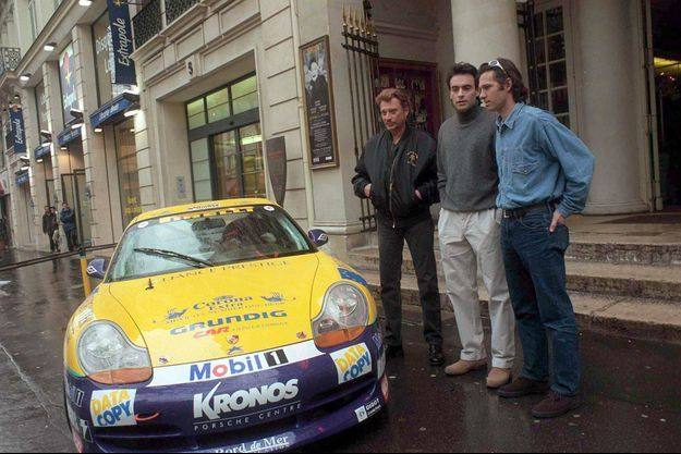Anthony Delon, Paul Belmondo, Johnny Hallyday devant une Porsche.