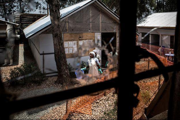 Des agents de santé à travers un trou de balle dans la fenêtre d'un centre de traitement pour Ebola, attaqué le 9 mars 2019 à Butembo.