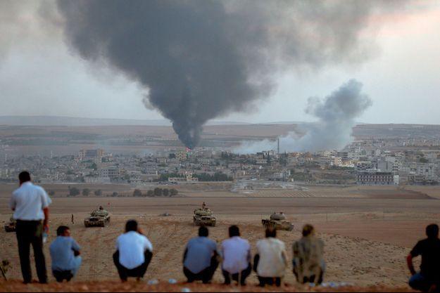 Le 9 octobre 2014, près de Suruç, à la frontière turco-syrienne. Derrière les chars turcs immobiles, des Kurdes, témoins impuissants de la bataille de Kobané.