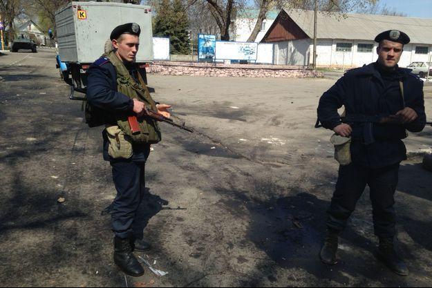 Des membres de la garde nationale surveillent l'entrée de la base de Marioupol, au milieu des débris de l'attaque.