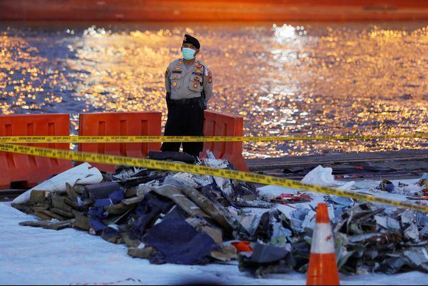 Un policier devant des débris du vol Lion Air.