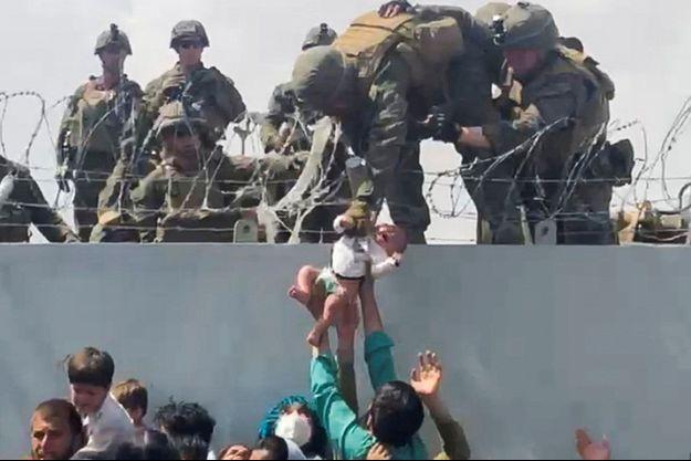 Cette photo a fait le tour du monde: un bébé est évacué par des militaires américains alors qu'une cohue s'est formée devant le mur extérieur de l'aéroport de Kaboul.