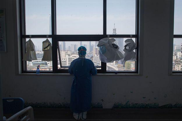 Un soignant chinois contemple l'extérieur depuis un hôpital de Wuhan. Image d'illustration.