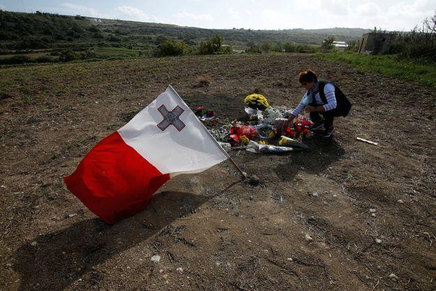 Un drapeau maltais et des fleurs à l'endroit où Daphne Caruana Galizia a été assassinée.
