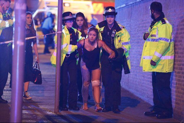 Une victime sort de la salle de concert où a eu lieu l'explosion.
