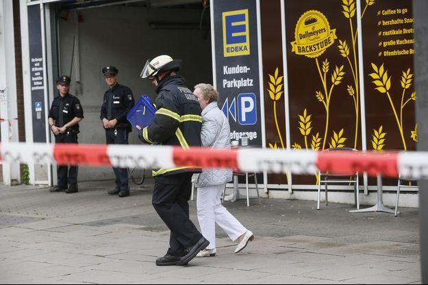 Les policiers et un pompier devant le supermarché où l'attaque a eu lieu vendredi, à Hambourg.