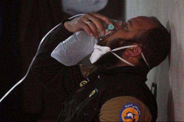 Un membre de la défense civile tente de reprendre de l'oxygène après avoir été des victimes d'une attaque au gaz