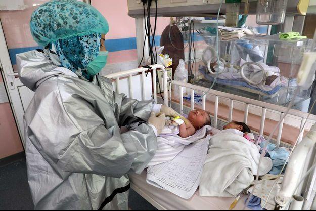 Une infirmière prend soin des bébés qui ont perdu leurs mères durant l'attaque de la maternité, à Kaboul, le 13 mai.