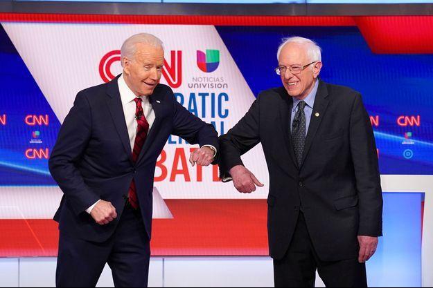 Joe Biden et Bernie Sanders se saluent sans se serrer la main lors d'un débat à Washington, le 15 mars, alors que les premières mesures de distanciation sociale étaient mises en place aux Etats-Unis.