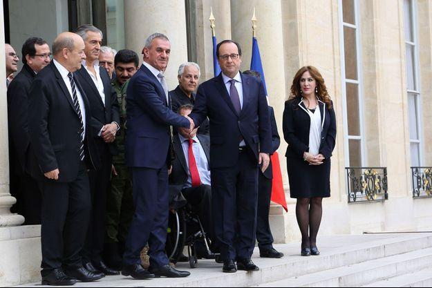 Le Président François Hollande salue le ministre kurde des peshmergas Mustafa Qadir Mustafa sur le perron de l'Elysée le mercredi 1er avril 2015, à l'issue d'une réunion d'une heure avec une délégation kurde en présence du ministre de la Défense, JeanYves Le Drian (à gauche) et du philosophe Bernard-Henri Levy (au fond à gauche)