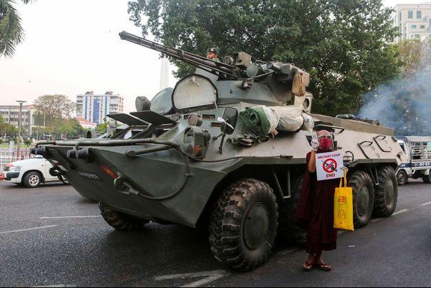 Un moine bouddhiste tient une pancarte appelant à la fin du coup d'état devant un char de l'armée, à Rangoun, en Birmanie, le 14 février 2021.