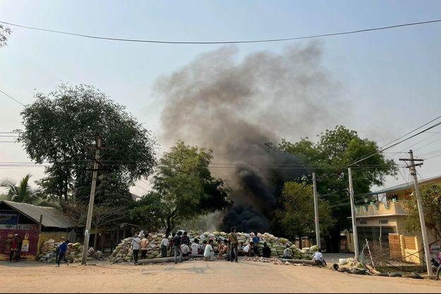 Les manifestants se rassemblent derrière une barricade lors d'une manifestation contre le coup d'État militaire, à Monywa, en Birmanie.