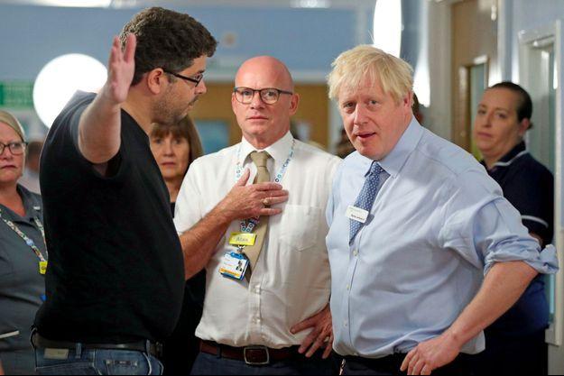 """Boris Johnson face à un père en colère lors de la visite d'un hôpital, mercredi à Londres. Devant les journalistes, il a affirmé au citoyen mécontent : """"Il n'y a pas de presse ici""""."""