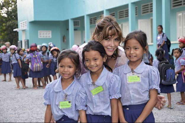 Tina Kieffer entourée d'élèves de primaire. L'uniforme compte des chemises de deux couleurs que les familles doivent changer en milieu de semaine : une façon de les éduquer à l'hygiène.