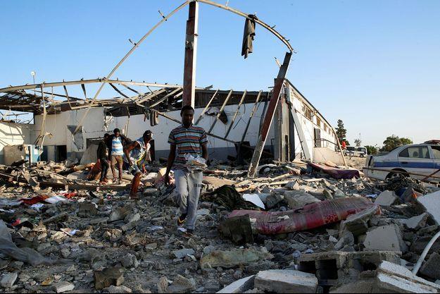 Des migrants ramassent leurs affaires dans les décombres du centre de détention, à Tajoura, en Libye.
