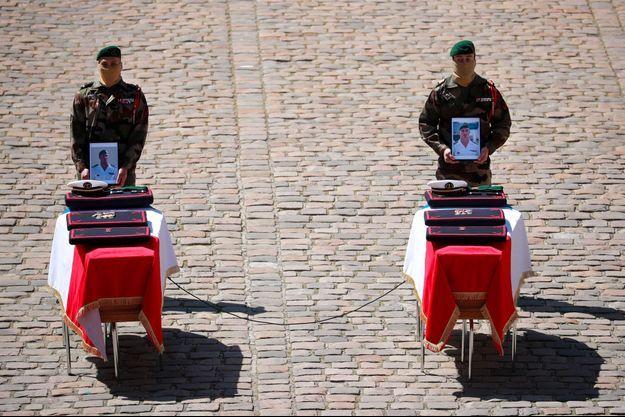 Des soldats du commando Hubert présentent des portraits de Cédric de Pierrepont et Alain Bertoncello, lors de l'hommage aux deux soldats aux Invalides, mardi.