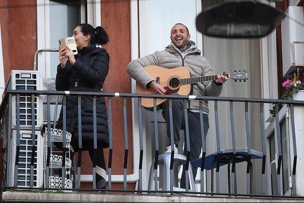 Un homme pousse la chansonnette au balcon de son appartement, à Milan, en Italie.