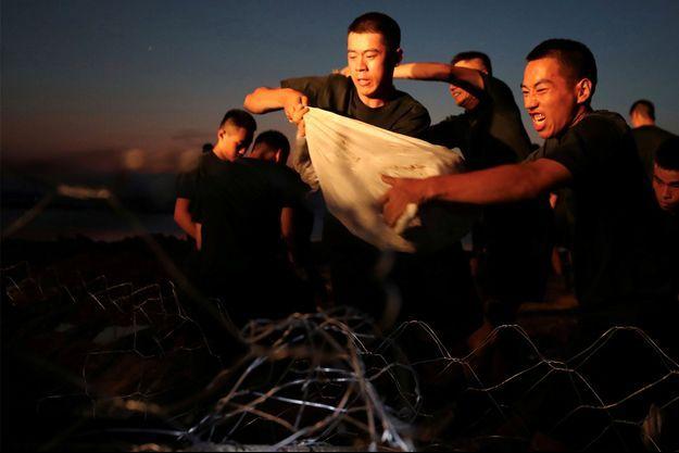 Des paramilitaires transportent des sacs de sable pour sceller une section de la digue le long de la rivière Wei qui avait éclaté et inondé des maisons, à la suite de fortes pluies à Xinxiang, dans la province du Henan, en Chine, le 24 juillet 2021