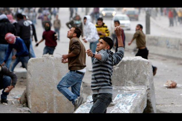 Jeunes Palestiniens lançant des pierres contre les forces d'occupation israéliennes à Kalandia près de Jérusalem.
