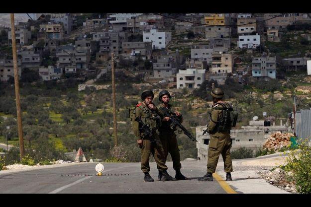 Un barrage de soldats israéliens près de Naplouse, dimanche. Les militaires tentent d'arrêter l'auteur de la tuerie.
