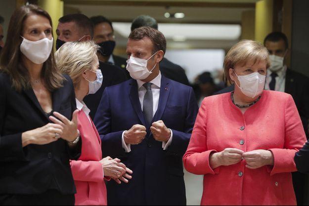 La Première ministre belge Sophie Wilmès, la présidente de la Commission européenne Ursula von der Leyen, le président français Emmanuel Macron, et la chancelière allemande Angela Merkel échangent avant le début du Conseil européen, à Bruxelles, vendredi.