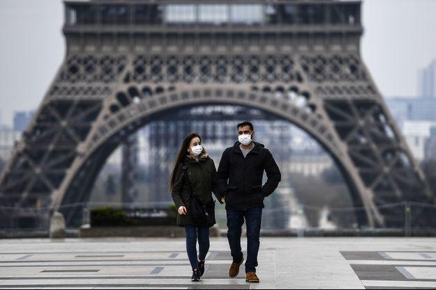 Un couple sur l'esplanade du Trocadéro à Paris, mercredi. Sur Google, l'intérêt pour les masques de protection a explosé ces derniers jours.