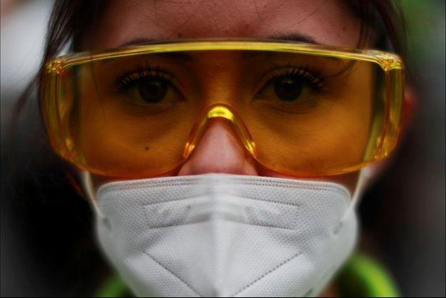 Une soignante prend part à une minute de silence en l'honneur de ses collègues mort du coronavirus à Mexico, le 30 mai 2020.