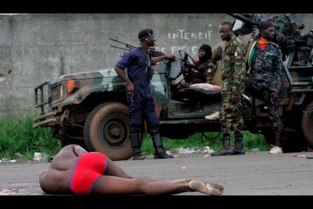 A Abidjan, des soldats loyaux au président Ouattara s'arrêtent devant un homme blessé, étendu sur la route.