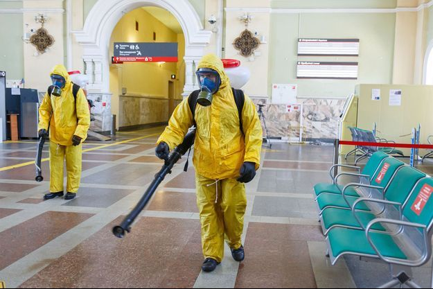 Un homme en tenue spéciale désinfecte la gare de Rizhsky, à Moscou.