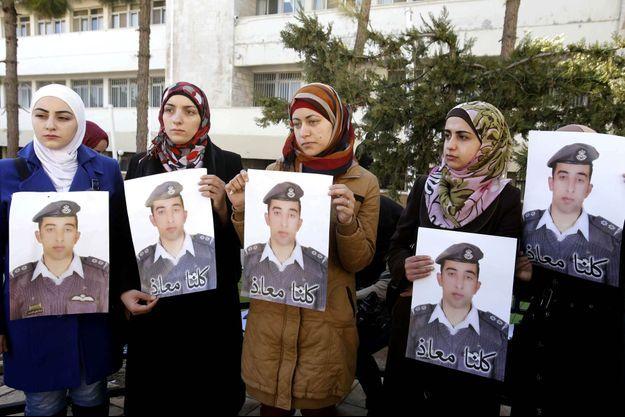 Anwar al-Tarawneh (au centre), l'épouse du lieutenant Muath al-Kaseasbeh, tenant son portrait, entourée de ses soutiens, à Amman, en Jordanie.