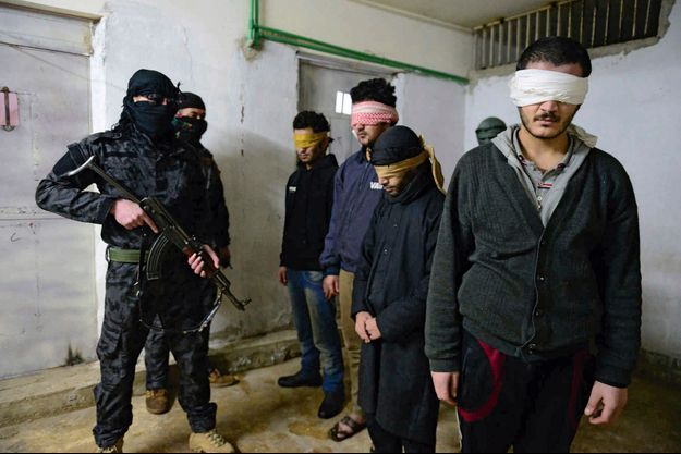 Dans le sous-sol d'un ex-commissariat de Til Koçer, lundi 15 décembre, quatre islamistes surveillés par des Kurdes qui restent masqués, pour éviter d'être identifiés par Daech.