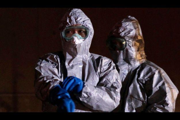 Près de la centrale de Fukushima, dimanche dernier. Les représentants des autorités portent des combinaisons protectrices.