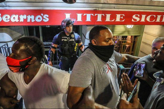 Un policier isolé protégé par des manifestants à Louisville.
