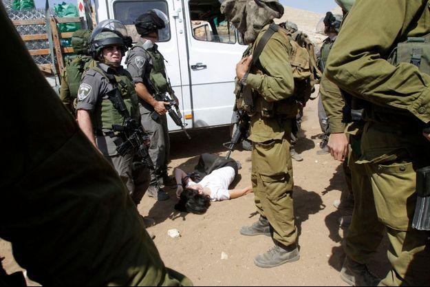 La diplomate française Marion Castaing, au sol, sous la surveillance des soldats israéliens.