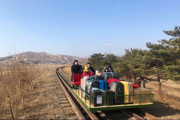 Les diplomates russes et leurs familles quittant la Corée du Nord sur un chariot ferroviaire.