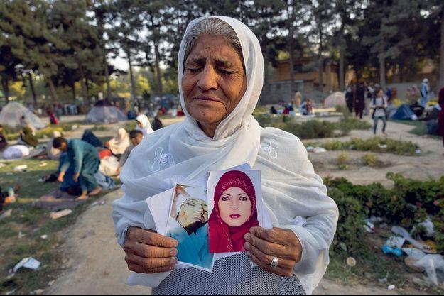 Zoohra, 60 ans, tient deux photos de sa fille tuée un mois plus tôt, dit-elle, par les talibans. Le 12 août, dans un camp de fortune pour les Afghans déplacés par le conflit, au parc Shahr-e Naw, à Kaboul.