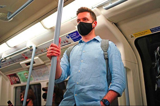 Un homme tient la main courante dans le métro londonien.