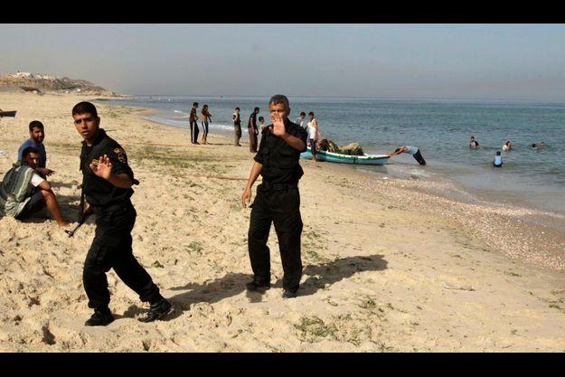 Des membres des forces de sécurité du Hamas sur une plage dans le centre de la bande de Gaza, au large de laquelle des militants palestiniens ont été tués par l'armée israélienne.