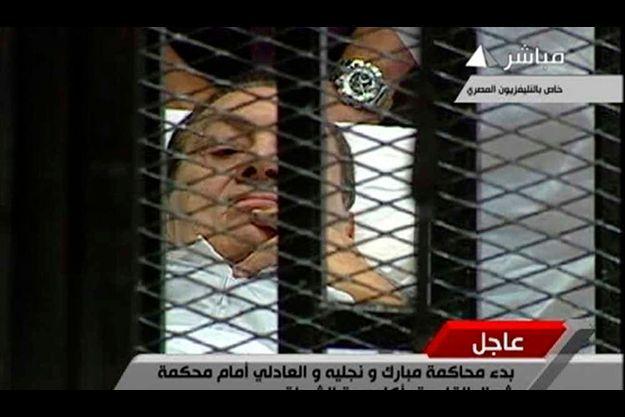 Hosni Moubarak, alité dans la cage faisant office de box des accusés.