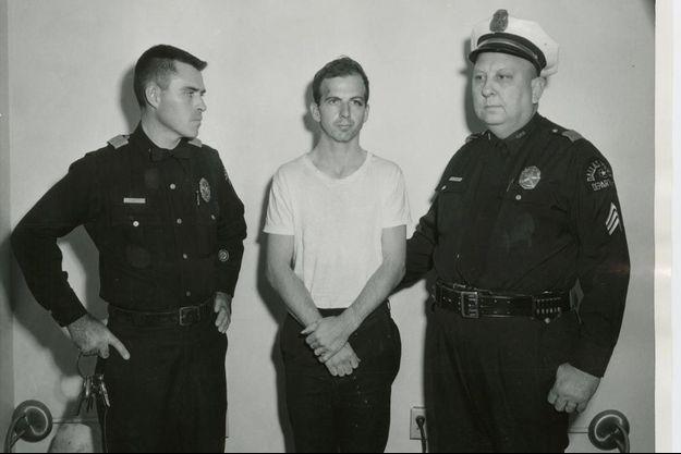 Lee Harvey Oswald entre deux policiers, peu après son arrestation.