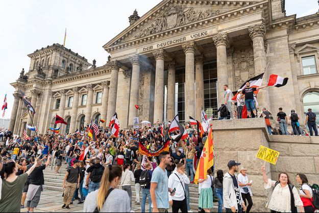 Manifestants anti-masques devant le Reichstag, à Berlin, samedi. Plusieurs drapeaux de l'ancien reich (noir, blanc et rouge) sont visibles.