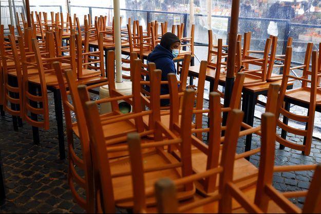 Un homme assis entre les chaises d'un restaurant fermé en Italie.