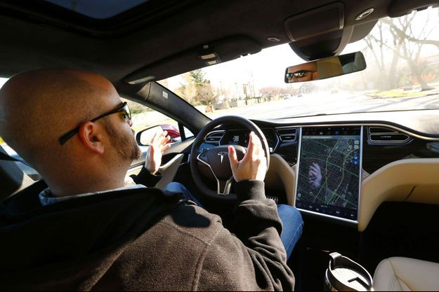 Un conducteur teste la fonctionnalité Autopilot à bord d'une Tesla Model S, en décembre 2015.