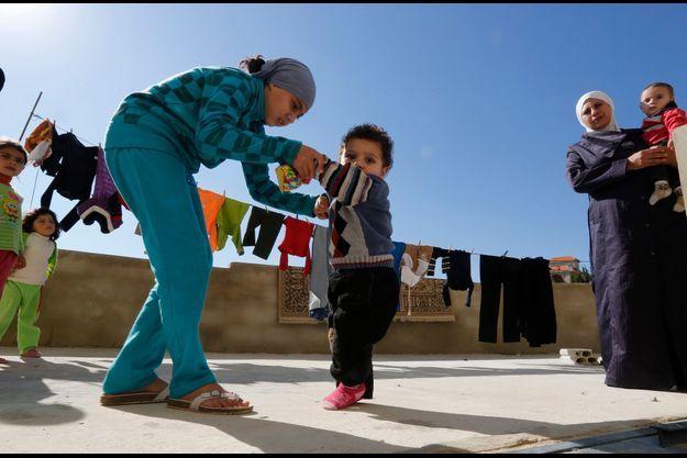 Un jeune réfugié syrien soupçonné d'avoir la polio aidé par sa soeur pour marcher, dans le camp de Chebaa, au Liban.