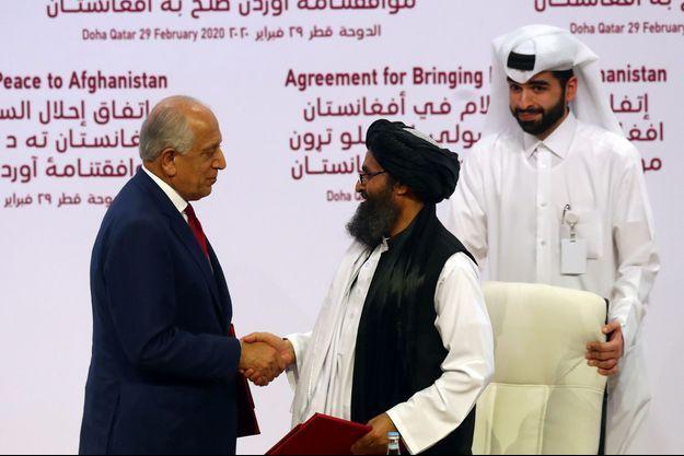 """Le négociateur américain Zalmay Khalilzad et le chef politique des talibans Abdul Ghani Baradar ont signé le texte et se sont serré la main, sous les applaudissements et des cris """"Allah Akbar (Dieu est le plus grand)""""."""
