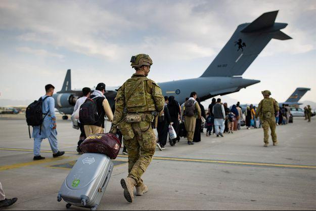 Les citoyens australiens et les titulaires de visa se préparent à monter à bord de l'avion C-17A Globemaster III de la Royal Australian Air Force, alors que le personnel d'infanterie de l'armée australienne assure la sécurité et assiste le fret, à l'aéroport international Hamid Karzai de Kaboul, le 22 août. (Image d'illustration)
